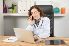 Manipulera kvinnan som talar på telefonen och skriver bärbara datorn Royaltyfria Foton