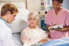 Manipulera med sjuksköterskan som talar till hög kvinnlig tålmodig i säng Arkivbild