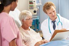 Manipulera med sjuksköterskan som talar till hög kvinnlig tålmodig i säng Arkivfoton