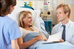 Manipulera med sjuksköterskan som talar till tonårs- kvinnlig tålmodig i säng Arkivbild