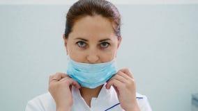 Manipulera pålagt en framsida en medicinsk maskering i en cosmetologyklinik stock video