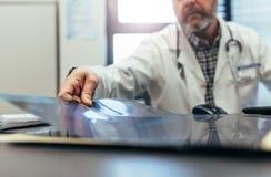 Manipulera sammanträde i hans klinik och undersökande medicinska bildläsning royaltyfria bilder