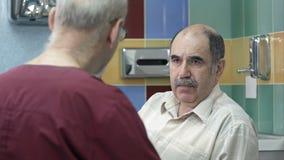 Manipulera samtal till den höga manliga patienten på kontoret stock video