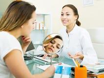 Manipulera samtal till den kvinnliga besökaren i estetisk medicinmitt royaltyfri bild