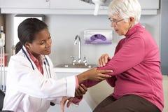 Manipulera undersökande kvinnlig tålmodig med armbågar smärtar Royaltyfri Fotografi
