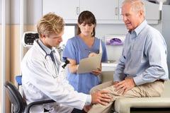 Manipulera undersökande Male tålmodig med knäet smärtar Royaltyfri Foto