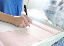Manipulera undersöker patientens ECG och skriver beskrivningen Royaltyfri Foto