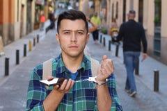 Manipulujący młody człowiek zakładający kajdanki jego telefon obraz stock