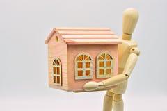 Maniquí de madera llevando una casa