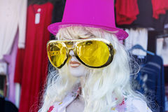 Maniquí con el sombrero rosado y las gafas de sol amarillas grandes Imágenes de archivo libres de regalías
