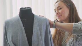 Maniquí de la adaptación y una costurera diseñador de sexo femenino en estudio Imagen de archivo libre de regalías
