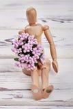 Maniquí de madera con las flores Foto de archivo