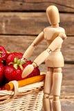 Maniquí de madera con las fresas maduras frescas fotografía de archivo libre de regalías