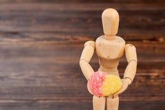 Maniquí de madera que sostiene el caramelo azucarado imagenes de archivo
