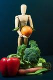 Maniquí de madera y una mezcla de verduras y de frutas Foto de archivo