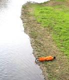 maniquí de un hombre con el mono anaranjado en la orilla del río Imágenes de archivo libres de regalías