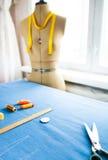 Maniquí del sastre con las cintas métricas en estudio de la moda imagenes de archivo