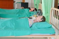 Maniquí médico en hospital, educación médica de entrenamiento del curso en cama y verde de la manta foto de archivo