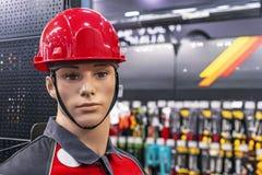 Maniquí masculino en un casco protector y ropa de trabajo foto de archivo
