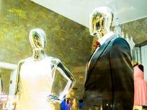 Maniquíes brillantes, anónimos en ventana de tienda Imágenes de archivo libres de regalías