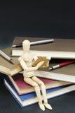 Maniqui czytelniczy obsiadanie na górze książki i pióra Obraz Stock