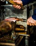 Maniscalco che martella ferro di cavallo immagini stock libere da diritti