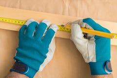 Manitas del carpintero que usa el lápiz para marcar el tablón imagenes de archivo