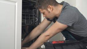 Manitas en los guardapolvos que reparan el lavaplatos nacional almacen de metraje de vídeo