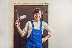 Manitas joven que instala la puerta con una espuma del montaje en un cuarto imagen de archivo