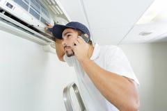 Manitas joven que repara el sistema de aire acondicionado que pide ayuda fotografía de archivo