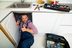 Manitas Lying On Floor que repara el fregadero en cocina Imagenes de archivo