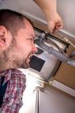Manitas Lying On Floor que repara el fregadero en cocina Foto de archivo