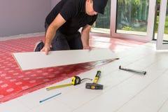 Manitas que instala el nuevo piso laminado fotografía de archivo