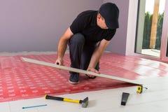 Manitas que instala el nuevo piso laminado foto de archivo libre de regalías