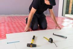 Manitas que instala el nuevo piso laminado imagen de archivo libre de regalías