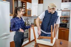 Manitas que repara los muebles en la cocina Él repara una silla con un destornillador Imágenes de archivo libres de regalías
