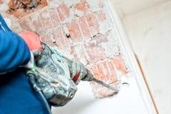 Manitas que usa un martillo perforador a los muros de cemento distroy Foto de archivo