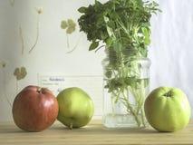 A manjericão com folhas pequena Balkon protagoniza em um frasco de vidro com maçãs da árvore em uma tabela fotografia de stock royalty free