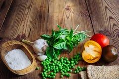 Manjericão, tomates da cor, alho, ervilhas verdes, sal e pão estaladiço Imagens de Stock Royalty Free
