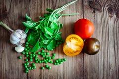 Manjericão, tomates da cor e alho, ervilhas verdes Foto de Stock Royalty Free