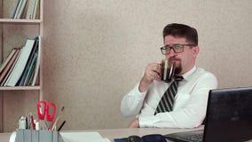Mankontorschef med ett skägg och exponeringsglas, lyckligt dricka kaffe lager videofilmer