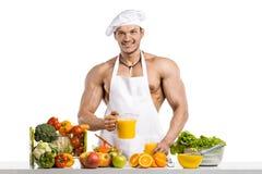 Mankroppsbyggarekock och att laga mat nytt sammanpressad fruktsaft och vegetab arkivfoto
