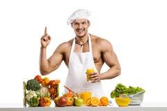Mankroppsbyggarekock och att laga mat nytt sammanpressad fruktsaft och vegetab arkivbild