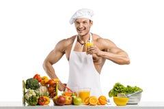 Mankroppsbyggarekock och att laga mat nytt sammanpressad fruktsaft och vegetab royaltyfria foton
