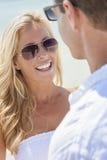 Mankvinnapar i solglasögon på stranden Fotografering för Bildbyråer