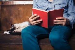 Manläsning på soffan med katten Royaltyfria Bilder