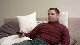 Manlögner i säng håller ögonen på television och att le lager videofilmer