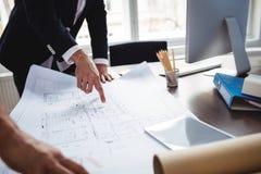 Manle binnenlandse ontwerper die blauwdruk bespreken met medewerker stock foto