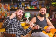 Manlekgitarr i bar Konsert f?r levande musik Akustisk kapacitet i bar Brutalt f?r Hipster som upps?kas med v?nnen i bar royaltyfri fotografi
