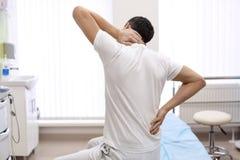 Manlidande från hals smärtar i ortopedens kontor arkivbilder